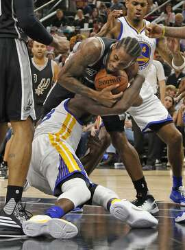 SAN ANTONIO,TX - APRIL 10: Kawhi Leonard #2 of the San Antonio Spurs outfights Draymond Green #23 of the Golden State Warriors for a loose ball at AT&T Center on April 10, 2016 in San Antonio, Texas.  NOTE TO USER: User expressly acknowledges and agrees that , by downloading and or using this photograph, User is consenting to the terms and conditions of the Getty Images License Agreement. (Photo by Ronald Cortes/Getty Images)