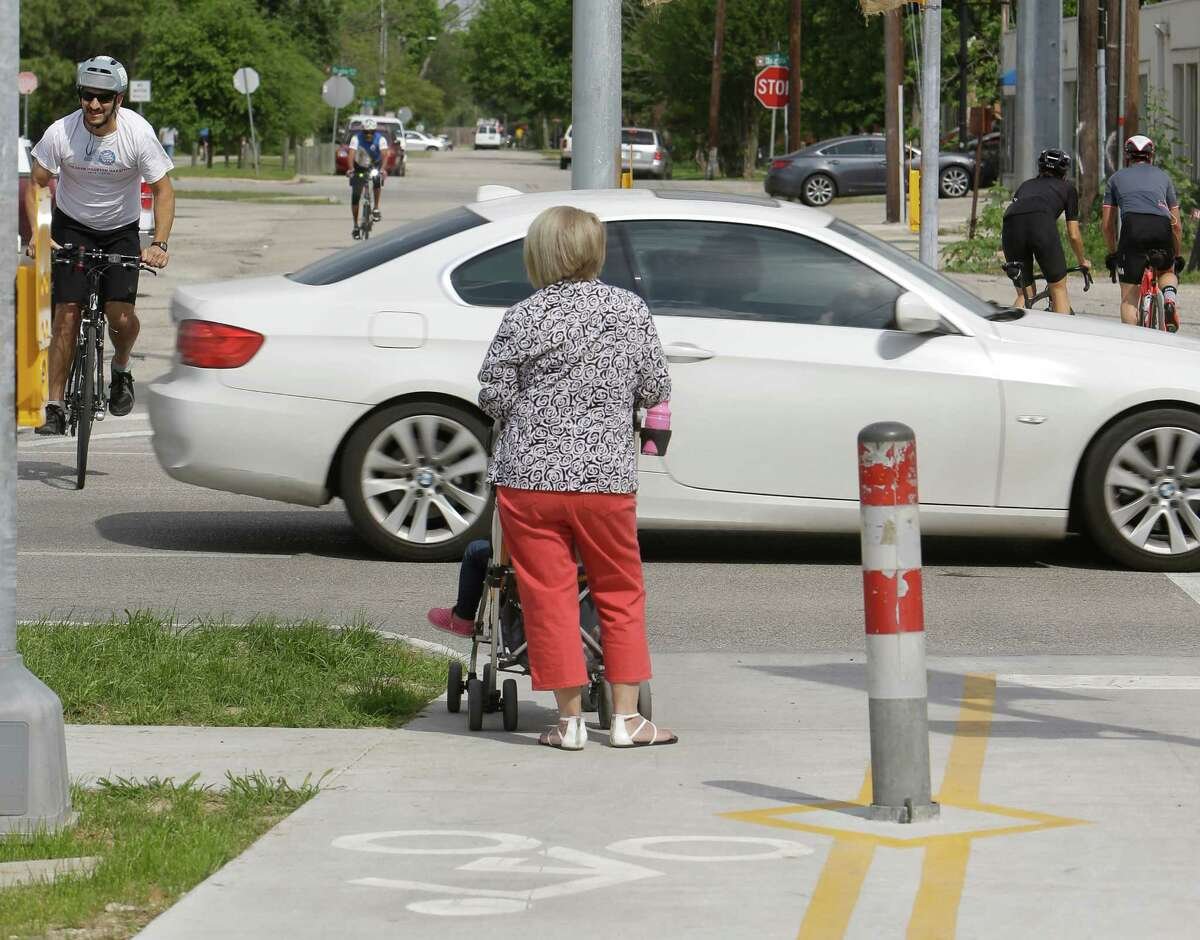 People are shown at the intersection of Yale and the Heights Hike and Bike Trail on April 6, at 7th. A new light will mean cyclists and joggers do not have to wait for a break in the traffic.