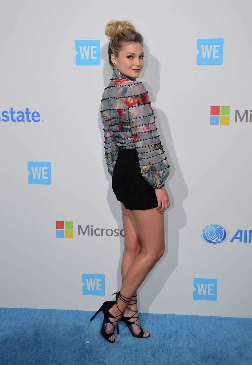 Olivia Holt poses on arrival for WE Day in California on April 7, 2016 in Los Angeles, California, where some 16,000 students and educators from over 550 schools across the state came to celebrate their commitment to taking actions on issues they care about. / AFP / FREDERIC J. BROWN