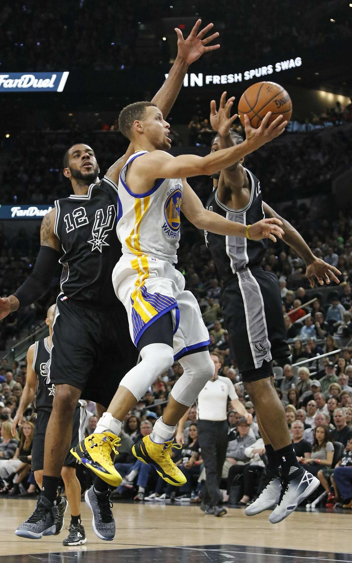 SAN ANTONIO,TX - APRIL 10: Stephen Curry #30 of the Golden State Warriors scores between LaMarcus Aldridge #12 and Kawhi Leonard #2 of the San Antonio Spurs at AT&T Center on April 10, 2016 in San Antonio, Texas. The Warriors won 92-86, tying the all-time record for wins in a season with 72. NOTE TO USER: User expressly acknowledges and agrees that , by downloading and or using this photograph, User is consenting to the terms and conditions of the Getty Images License Agreement. (Photo by Ronald Cortes/Getty Images)