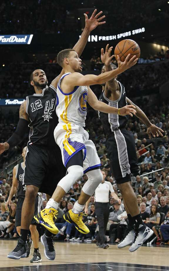 SAN ANTONIO,TX - APRIL 10: Stephen Curry #30 of the Golden State Warriors scores between LaMarcus Aldridge #12 and Kawhi Leonard #2 of the San Antonio Spurs at AT&T Center on April 10, 2016 in San Antonio, Texas. The Warriors won 92-86, tying the all-time record for wins in a season with 72. NOTE TO USER: User expressly acknowledges and agrees that , by downloading and or using this photograph, User is consenting to the terms and conditions of the Getty Images License Agreement. (Photo by Ronald Cortes/Getty Images) Photo: Ronald Cortes, Getty Images