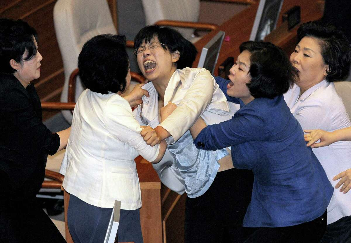 A female opposition legislator screams after being dragged away by ruling party lawmakers during a scuffle in parliament in Seoul on July 22, 2009. After the scuffles which left dozens of people injured, the ruling Grand National Party raidroaded bills designed to ease curbs on media ownership. AFP PHOTO/JUNG YEON-JE