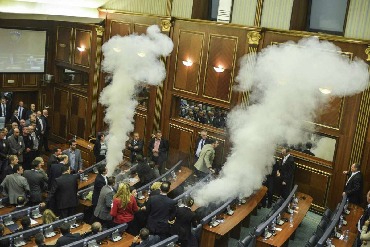 Kosovo parliamentary lawmakers step back as tear gas fills the chamber at Kosovo's parliament in Pristina on October 23, 2015 after being released by opposition lawmakers for the third session running in protest at a recent EU-brokered deal reached by the government with Serbia. Opposition members are angry over an accord brokered by the European Union in August between Kosovo's government and Serbia, which the EU had hailed as a