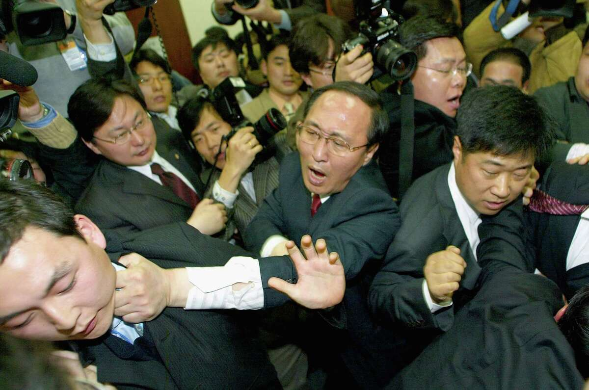 Members of South Korea's ruling Uri Party scuffle with opposition Grand National Party members during a move to present a controversial bill calling for the abolition of an aged anti-communist law through parliament at National Assembly on December 6, 2004 in Seoul, South Korea. The ruling party bill seeks to abolish the half century old National Security Law which the opposition pledges to block the motion by all means. (Photo by Chung Sung-Jun/Getty Images)
