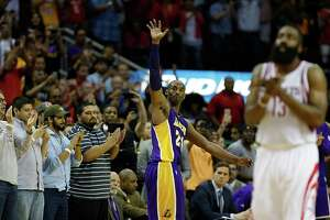 Los Angeles Lakers forward Kobe Bryant center, waves to the crowd as he leaves the game as Houston Rockets guard James Harden right, applauds near the end of the second half of NBA game action at the Toyota Center Sunday, April 10, 2016, in Pearland. ( James Nielsen / Houston Chronicle )