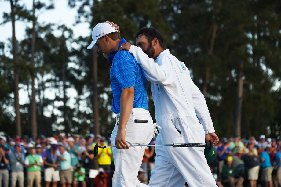 US golfer Jordan Spieth is comforted by his caddie Michim ael Greller as they leave the 18th green during Round 4 of the 80th Masters Golf Tournament at the Augusta National Golf Club on April 10, 2016, in Augusta, Georgia. England's Danny Willett won the 80th Masters at Augusta National for his first major title. He was trailing defending champion Jordan Spieth by five strokes around the turn, but stormed down the back nine to overhaul the American. Willett is the first Englishman since Nick Faldo 20 years ago to win the Masters and only the second all-time. / AFP PHOTO / Jim WatsonJIM WATSON/AFP/Getty Images Photo: JIM WATSON, AFP/Getty Images