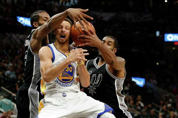 Spurs' Kawhi Leonard (02) and LaMarcus Aldridge (12) defend against Golden State Warriors' Stephen Curry (30) at the AT&T Center on Sunday, Apr. 10, 2016. The Warriors defeated the Spurs, 92-86. The Warriors with the victory also tied the 1995-96 Chicago Bulls for most wins in an NBA season with 72 victories. (Kin Man Hui/San Antonio Express-News)