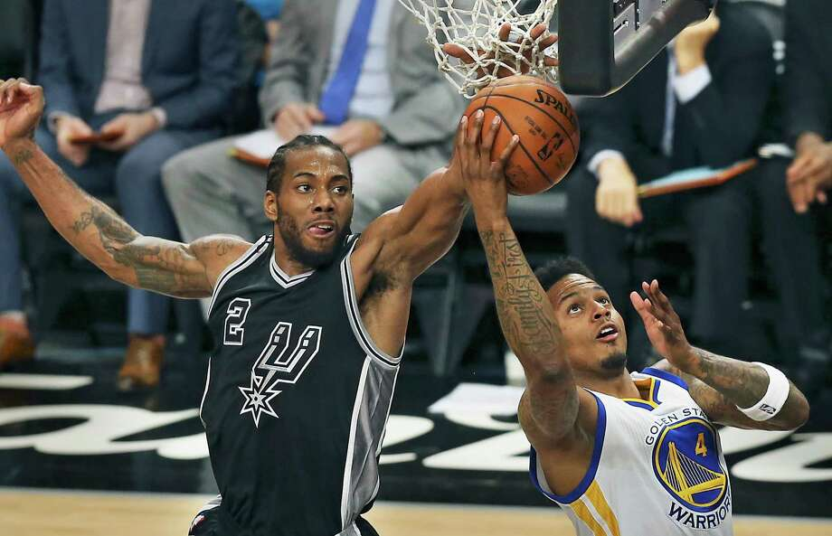 Kawhi Leonard gets in the net to block a shot by Brandon Rush Spurs host Golden State at the AT&T Center on April 10, 2016. Photo: TOM REEL, STAFF / SAN ANTONIO EXPRESS-NEWS / 2016 SAN ANTONIO EXPRESS-NEWS