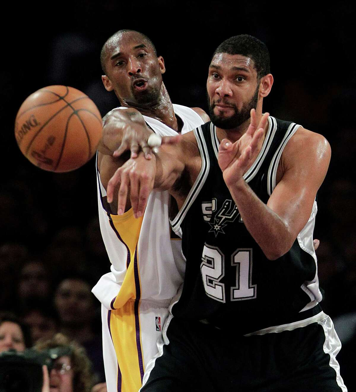 Spurs center Tim Duncan passes as he is pressured by Los Angeles Lakers guard Kobe Bryant during the first half on April 4, 2010.
