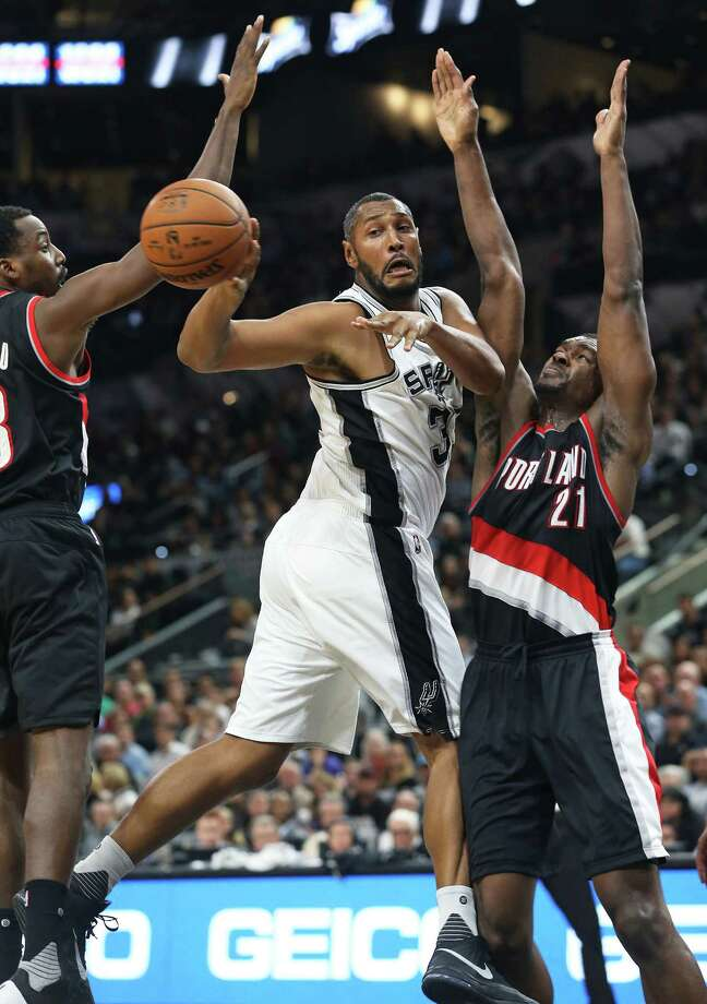 Boris Diaw passes to the outside after drawing Al-Farouq Amini (left) and Noah Vonleh into the paint as the Spurs host Portland at the AT&T Center on Nov. 16, 2015. Photo: Tom Reel /San Antonio Express-News / 2015 SAN ANTONIO EXPRESS-NEWS