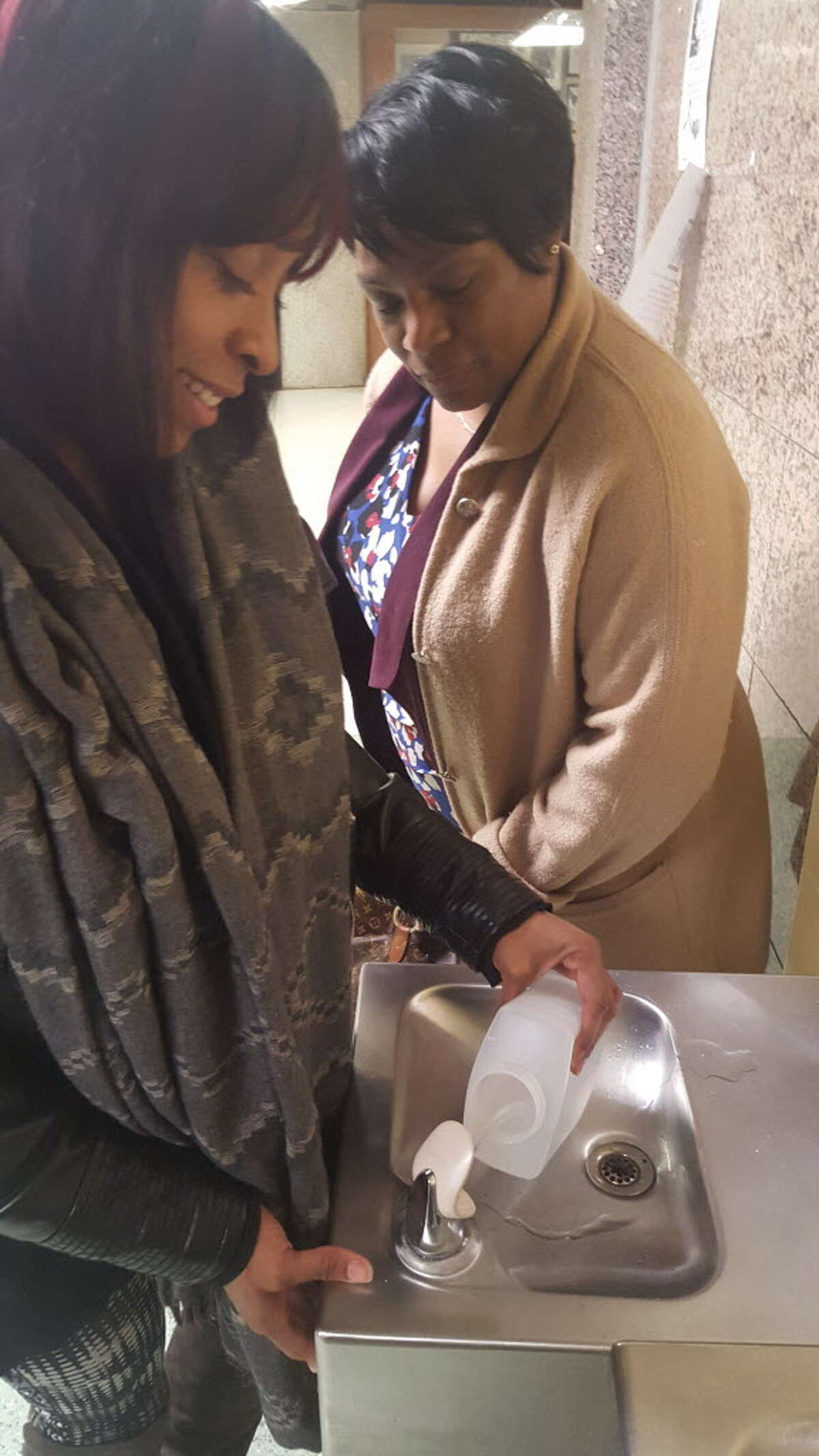 Jenifer Frazier, an epidemiological investigator for the Bridgeport Health Department's Lead Poisoning Prevention Program. left and Audrey Gaines, director of the Lead Poisoning Prevention Program for the city, show how they collected water to test for lead. They are demonstrating at Central High School, which has not yet been tested by the department.
