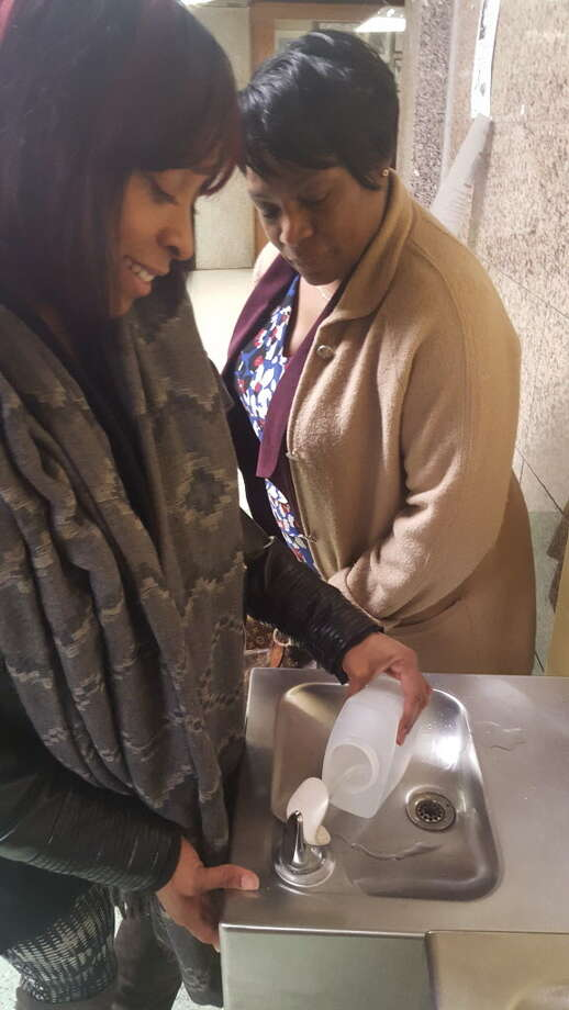 Jenifer Frazier, an epidemiological investigator for the Bridgeport Health Department's Lead Poisoning Prevention Program. left and Audrey Gaines, director of the Lead Poisoning Prevention Program for the city, show how they collected water to test for lead. They are demonstrating at Central High School, which has not yet been tested by the department. Photo: Contributed / Contributed