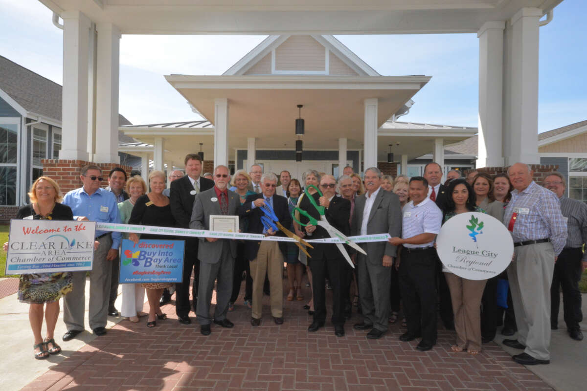 Senator Larry Taylor, front row, was joined with Methodist Retirement Communities Board Chair Rev. Jack Womack, front center, and The Crossings Board Chair Tom Wussow, front left, as they cut the ribbon during a dedication of The Crossings retirement community in League City.