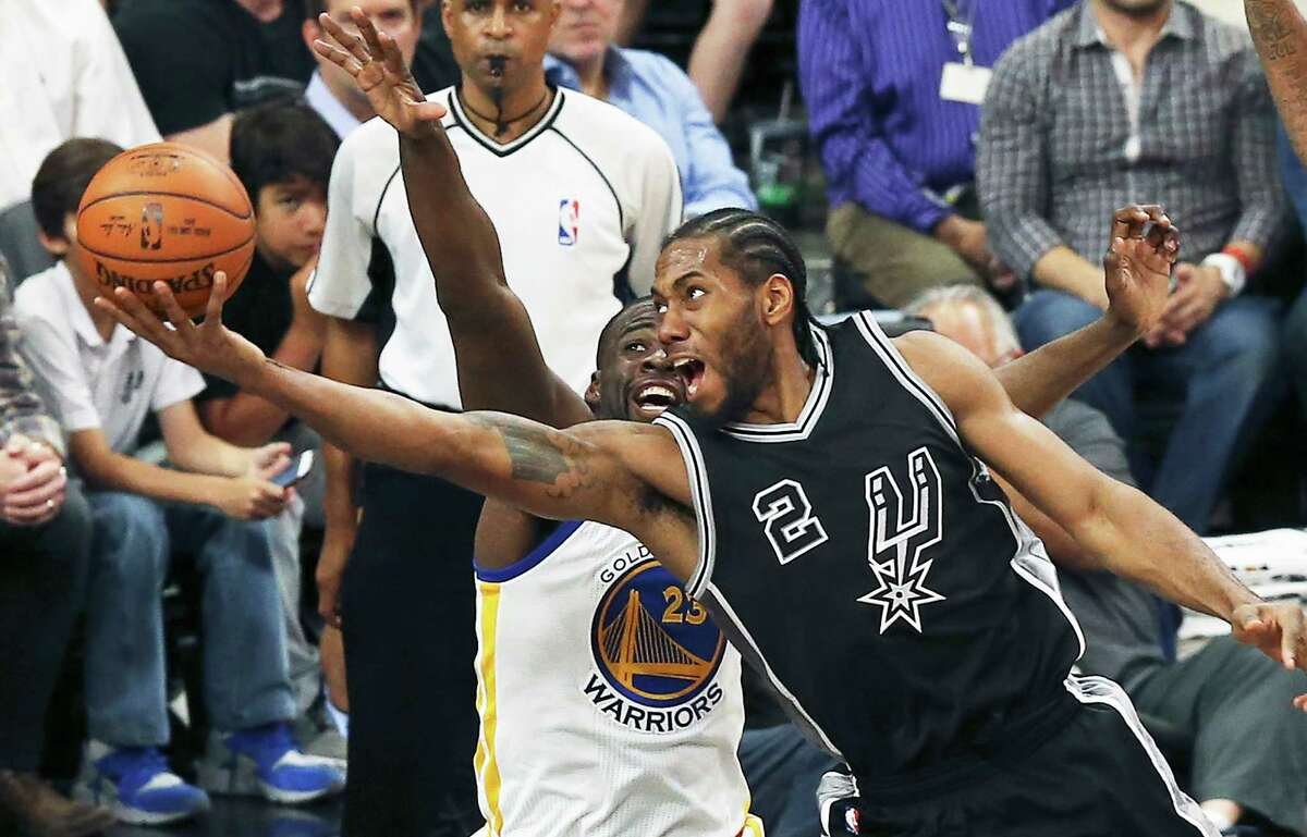 Kawhi Leonard stretches in to take a shot on Draymond Green as the Spurs host Golden State at the AT&T Center on April 10, 2016.