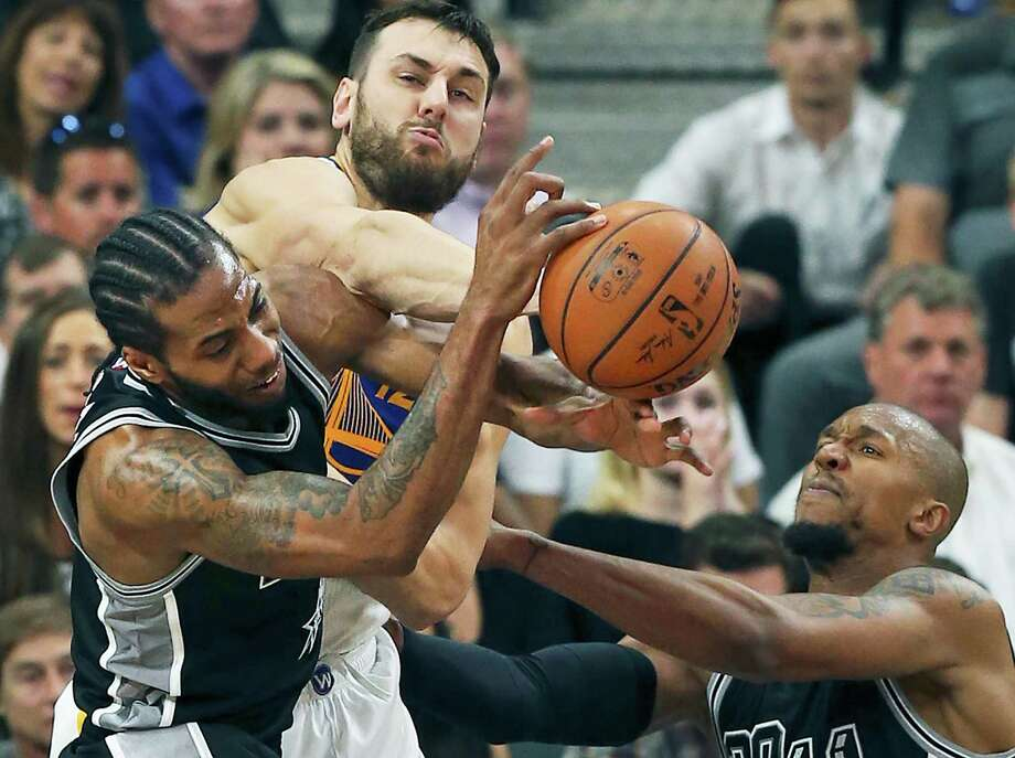 Andrew Bogut powers in to break up control of the ball for the Spurs' Kawhi Leonard and David WEst as the Spurs host Golden State at the AT&T Center on April 10, 2016. Photo: TOM REEL, STAFF / SAN ANTONIO EXPRESS-NEWS / 2016 SAN ANTONIO EXPRESS-NEWS