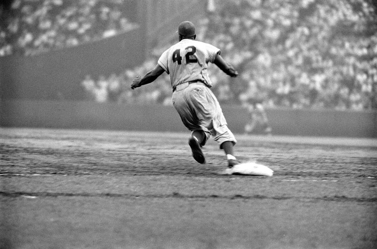 Jackie Robinson rounds first base looking for a double.
