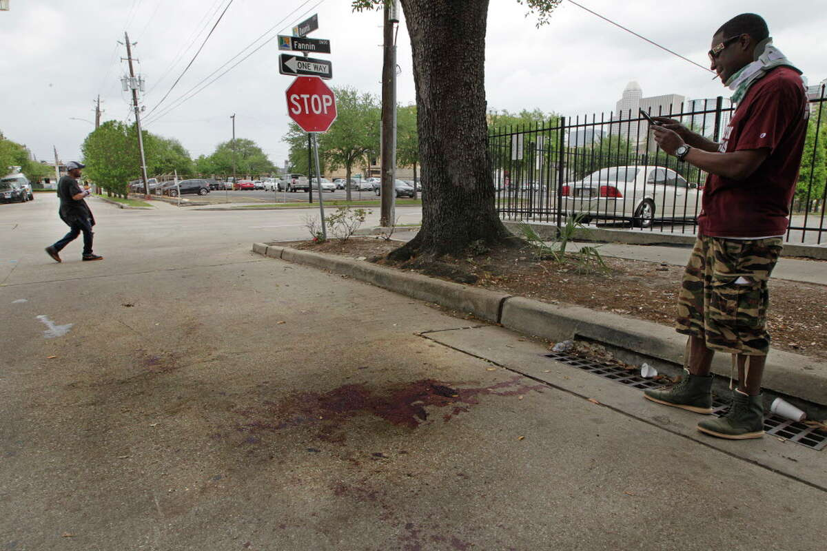 Ariel Johnson photographs the blood stains on Dennis Street where a double homicide happen Monday, April 11, 2016, in Houston's Midtown.