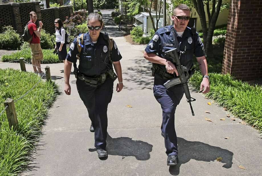 In this April 27, 2009 photo, University of Georgia police officers patrol the campus in Athens, Ga., with a semi-automatic rifle during a search for professor George Zinkhan, suspected of killing his ex-wife and two others near campus two days earlier. Federal data and Associated Press interviews and requests for records reveal that at least 100 college police agencies have added rifles over the past decade.   (John Spink/Atlanta Journal-Constitution via AP)  MARIETTA DAILY OUT; GWINNETT DAILY POST OUT; LOCAL TELEVISION OUT; WXIA-TV OUT; WGCL-TV OUT; MANDATORY CREDIT Photo: John Spink, AP