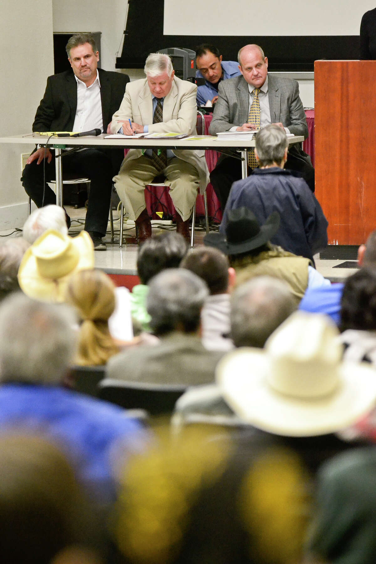 C.Y. Benavides III (from left), Pierce Chandler and John Shaw listen to concerns brought up by residents living near the proposed landfill site in Webb County at a 2013 hearing. Recently, the state gave it a draft permit to open.