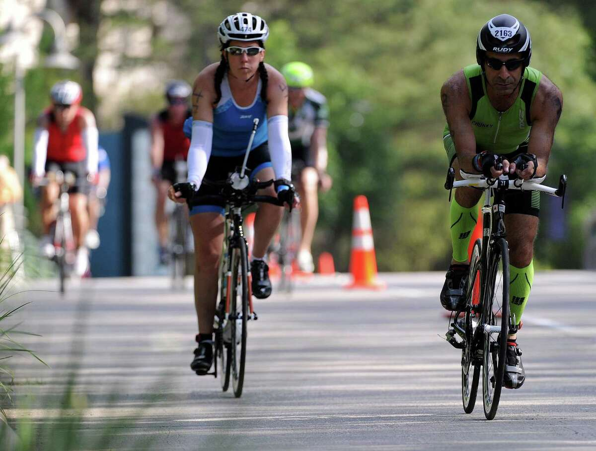 Tracy Hood, left, and Mehdi Balouchestani rode through the cycling segment during the Ironman North American Championship last year in The Woodlands.
