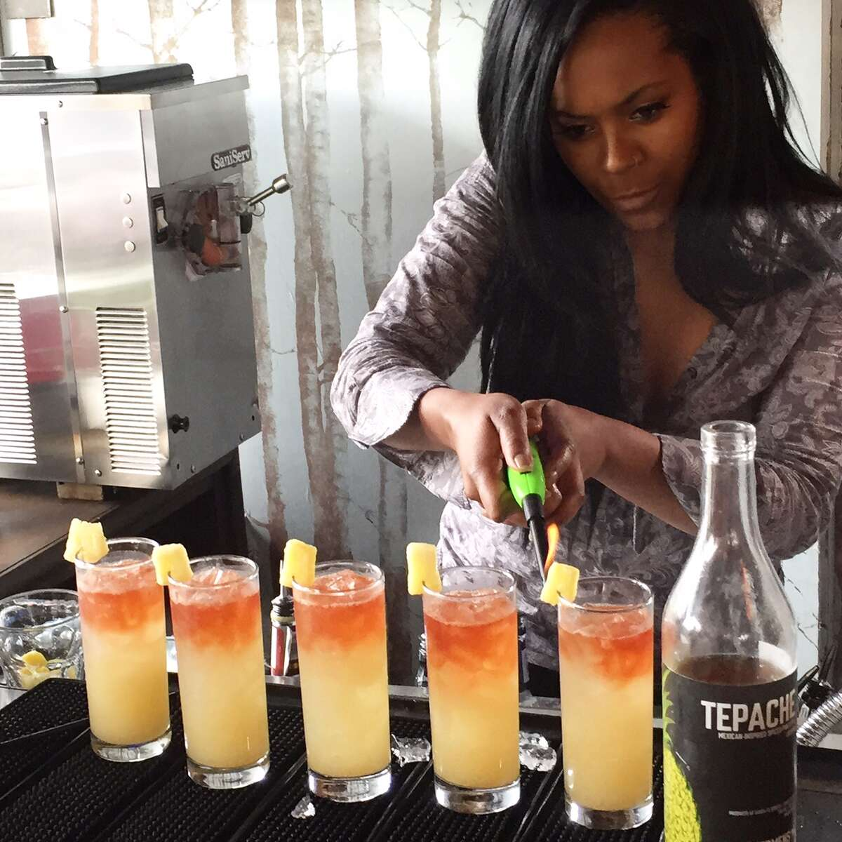 A competing bartender lights pineapple for Black Restaurant Week's Power of the Palette bartending competition on Saturday, April 9, 2016.