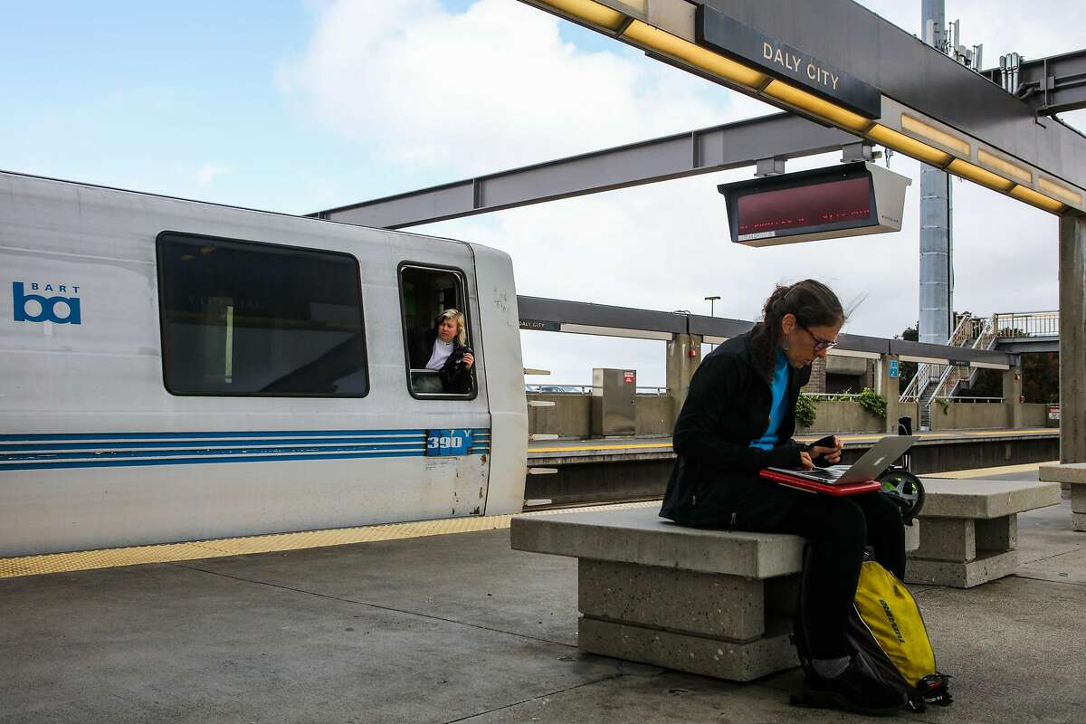 Nancy Gerber (right) works on her computer as a BART conductor looks to make sure all passengers have boarded the train, at the Daly City BART station, in Daly City, California, on Monday, April 11, 2016.