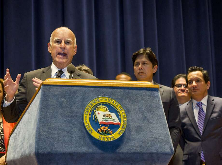 California Gov. Jerry Brown, left at podium, addresses members of the media, before signing a bill creating highest statewide minimum wage at $15 an hour by 2022 at the Ronald Reagan building in Los Angeles on Monday, April 4, 2016. Brown has said California, with the world's eighth largest economy, can absorb the raises without the problems predicted by opponents. (AP Photo/Damian Dovarganes) Photo: Damian Dovarganes, AP