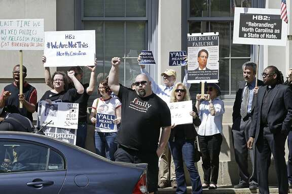 Opponents of House Bill 2 protest across the street from the North Carolina State Capitol in Raleigh, N.C., Monday, April 11, 2016 during a rally in support of the law that blocks rules allowing transgender people to use the bathroom aligned with their gender identity. (AP Photo/Gerry Broome)