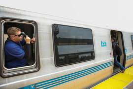 A BART conductor makes an announcement as passengers board the train at the Daly City BART stop in Daly City, California, on Monday, April 11, 2016.