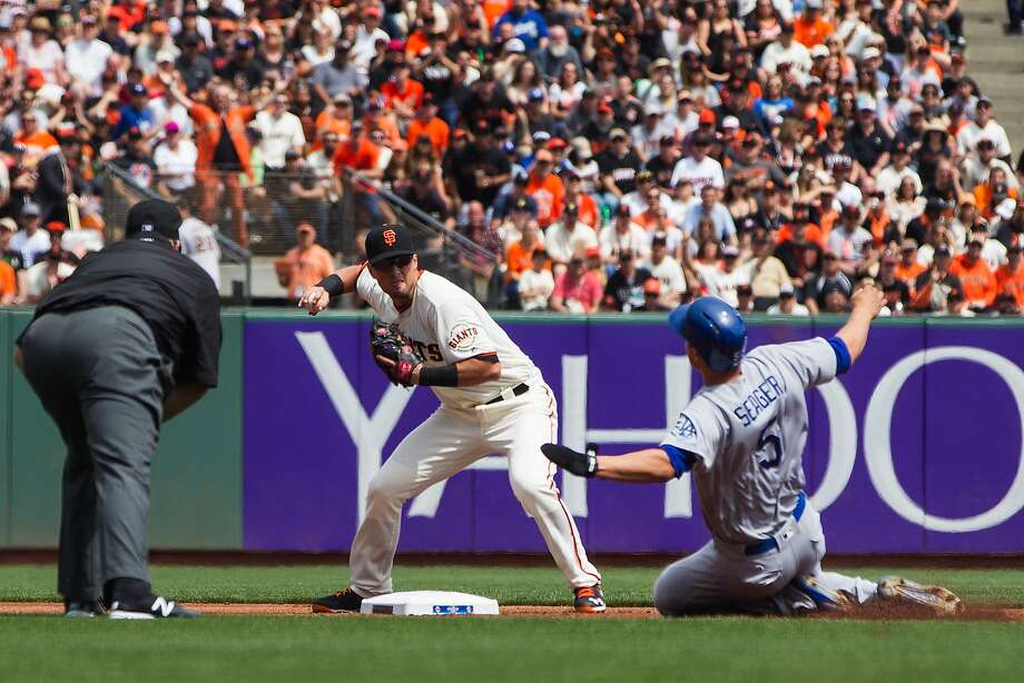 Giants second baseman Joe Panik, turning a double play Thursday as the Dodgers' Corey Seager slides toward him, doesn't like the new rules regarding plays at second. Photo: Jason O. Watson, Getty Images