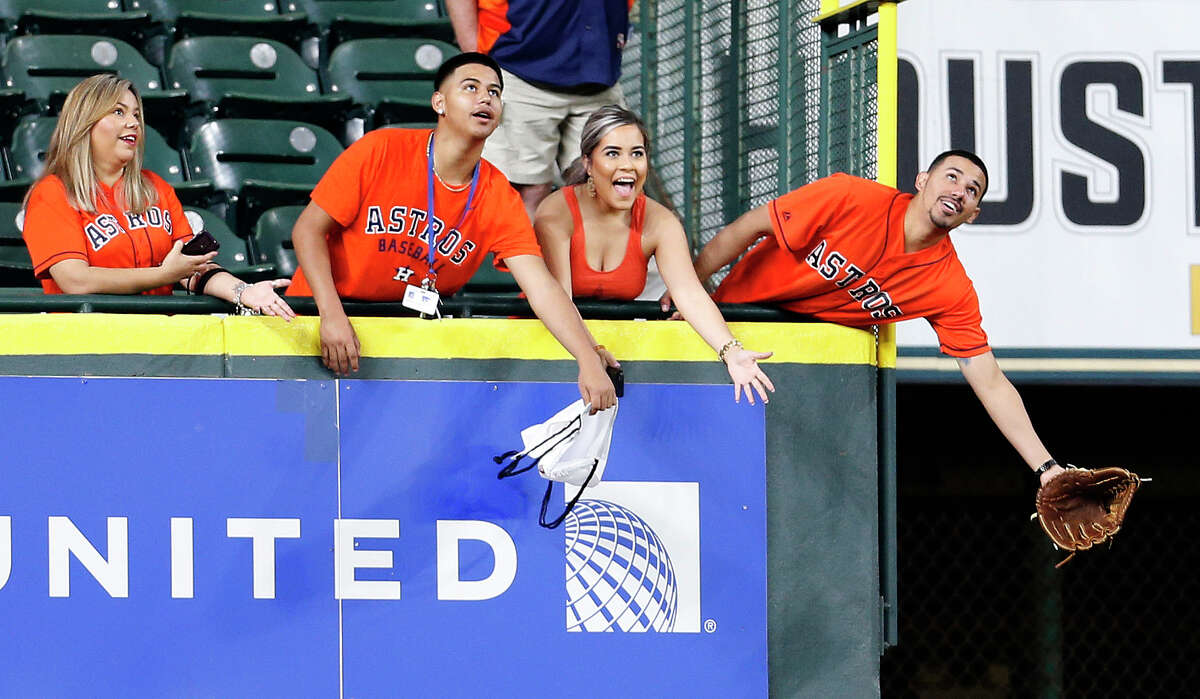 Houston Astros reaches for a ball in the Crawford Boxes during batting practice before the start of an MLB game at Minute Maid Park, Monday, April 11, 2016, in Houston.