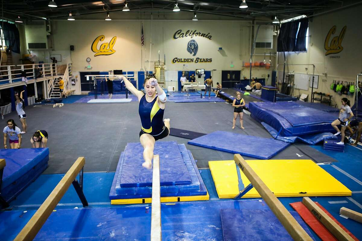 Cal gymnast Sofie Seilnacht (center) leaps through the air as she does a routine on the balance beams during practice at UC Berkeley, in Berkeley, California, on Thursday, April 7, 2016.