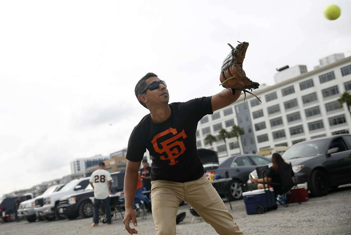 Raj Kang of Yuba City throws a ball with his cousin in a parking lot before Game 4 of the NLCS at AT&T Park on Wednesday, October 15, 2014 in San Francisco, Calif.