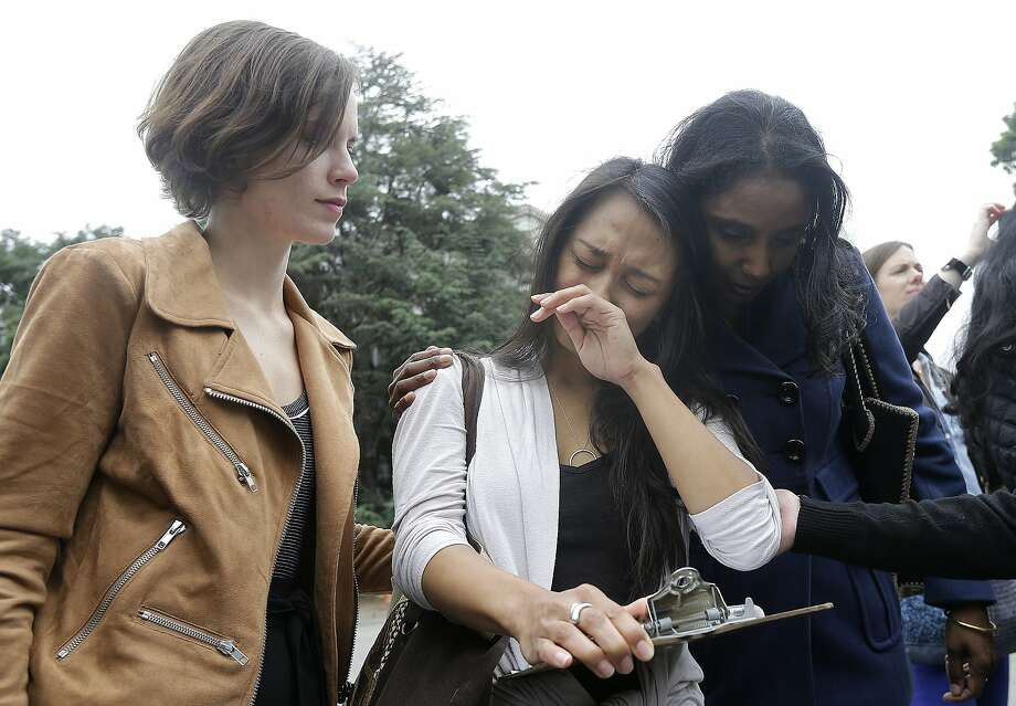 University of California graduate student Kathleen Gutierrez, center, is comforted by graduate student Erin Bennett, left, and Tyann Sorrell before all spoke at a news conference outside of Dwinelle Hall on the campus in Berkeley, Calif., Monday, April 11, 2016. Bennett and Gutierrez have filed a complaint regarding alleged sexual harassment by a University of California Berkeley professor. Sorrell has also made complaints against the same individual for sexual harassment. (AP Photo/Jeff Chiu) Photo: Jeff Chiu, AP