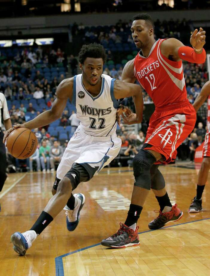 Minnesota Timberwolves guard Andrew Wiggins, left,  drives against Houston Rockets center Dwight Howard, right, during the first half of an NBA basketball game in Minneapolis, Monday, April 11, 2016. Photo: Ann Heisenfelt, AP / FR13069 AP