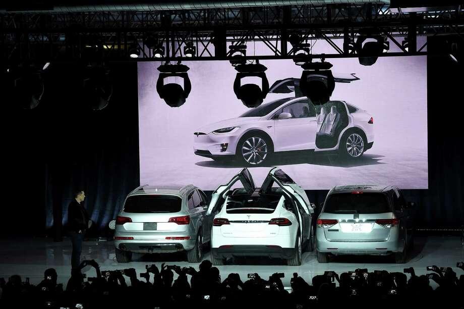 """(FILES) This file photo taken on September 29, 2015 shows Tesla CEO Elon Musk as he demonstrates how the doors work on the Tesla Model X  at the launch event in Femont, California. Tesla Motors is recalling 2,700 Model X sport utility vehicles to fix a locking hinge that could allow third-row seat backs to fold forward, the automaker said April 11, 2016. The recall affects SUVs bought before March 26.""""If a recliner were to slip during a crash, the seat back could move forward,"""" Tesla said in an email to owners of the luxury SUV with gull-wing rear doors.  / AFP PHOTO / SUSANA BATESSUSANA BATES/AFP/Getty Images Photo: SUSANA BATES, Stringer / AFP or licensors"""