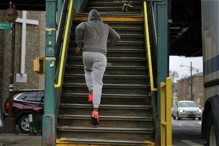 A person sprints up the stairs to an overhead subway platform on Roosevelt Ave. in New York, April 9, 2016. Impoverished New Yorkers tend to live far longer than their counterparts in other American cities, according to detailed new research, seeming to suggest that living in proximity to the preferences é' and tax base é' of wealthy neighbors may help improve well-being. (Nicole Bengiveno/The New York Times) Photo: NICOLE BENGIVENO, STF / NYTNS