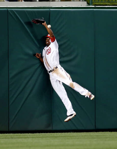 Nationals center fielder Michael Taylor can't bring down a fly ball hit by Atlanta's Nick Markakis that went for a double in the fifth inning of Monday's game at Washington. The Nationals won 6-4. Photo: Alex Brandon, STF