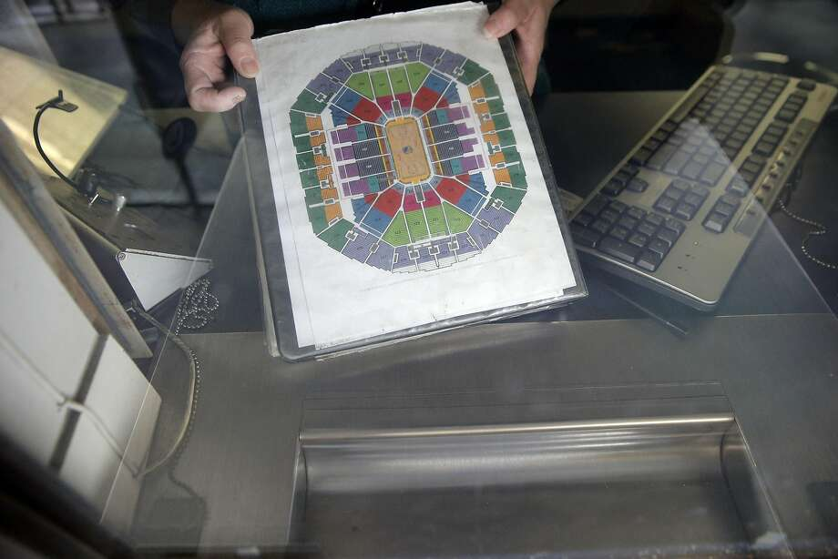 A ticket agent holds the Oracle Arena seating chart at the ticket counter. Photo: Carlos Avila Gonzalez, The Chronicle