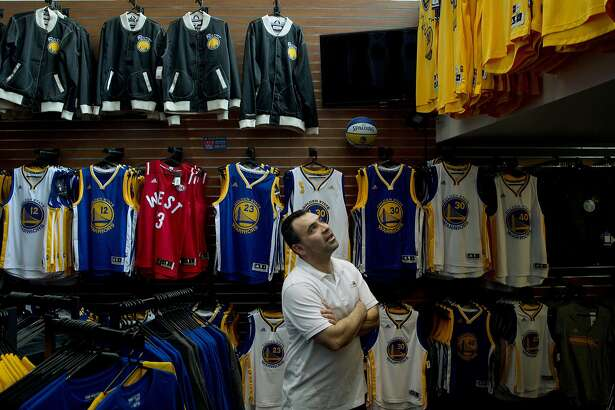 Robert Orellana looks up at jerseys at the Golden State Warriors team store at Oracle Arena in Oakland, Calif., on Monday, April 11, 2016.  A life-long Warriors fan, Orellana couldn't buy tickets for Wednesday's season finale and was looking at team merchandise instead.