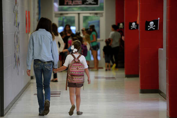 A high school students leads an elementary student to her classroom on the first day of school in Deweyville since flooding devastated the town in March. The district's elementary, middle and high school were consolidated to the high school campus.  Photo taken Monday 4/11/16 Ryan Pelham/The Enterprise