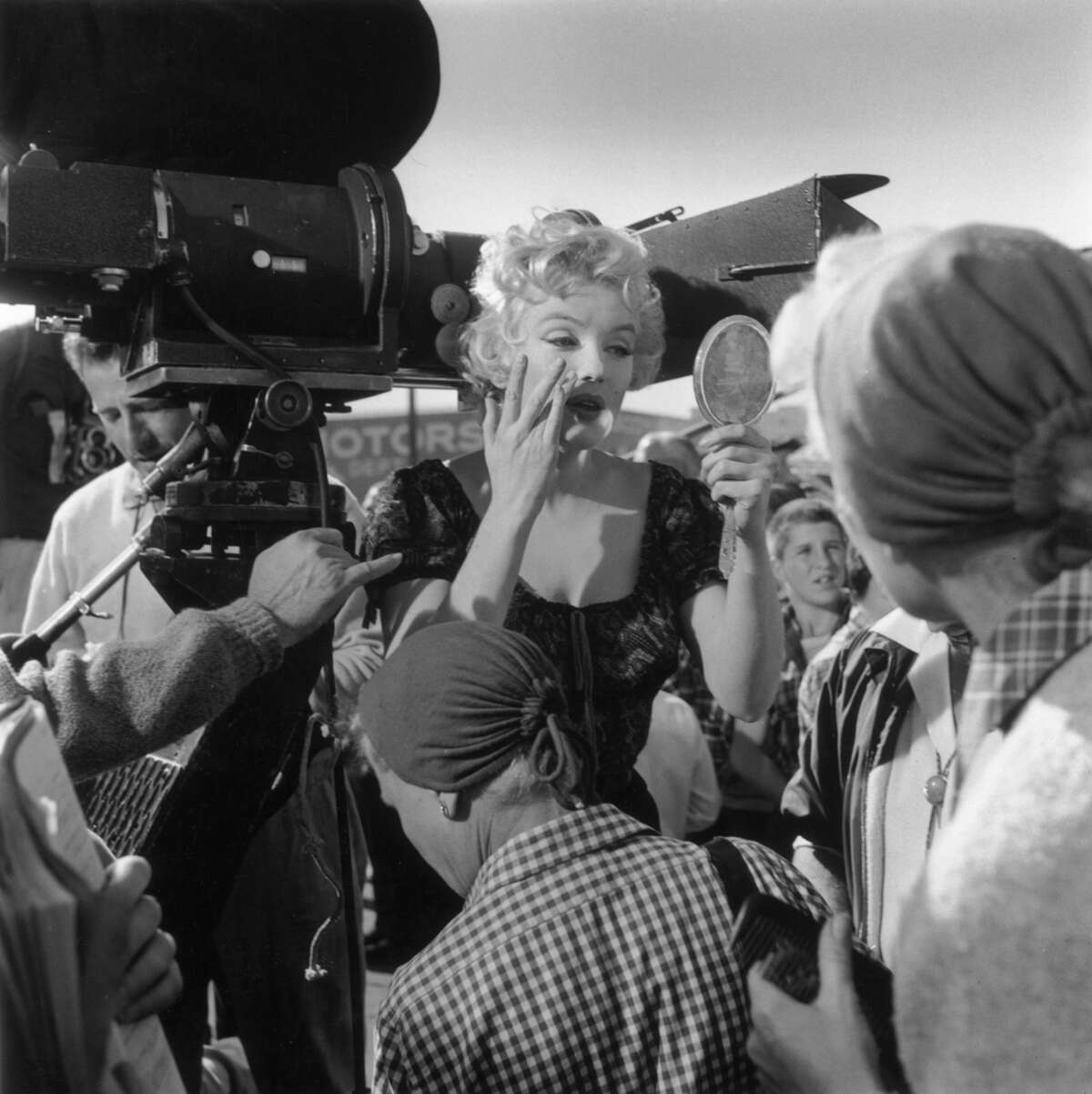 Marilyn Monroe adjusts her make-up, using a handheld mirror on the set of director Joshua Logan's film,