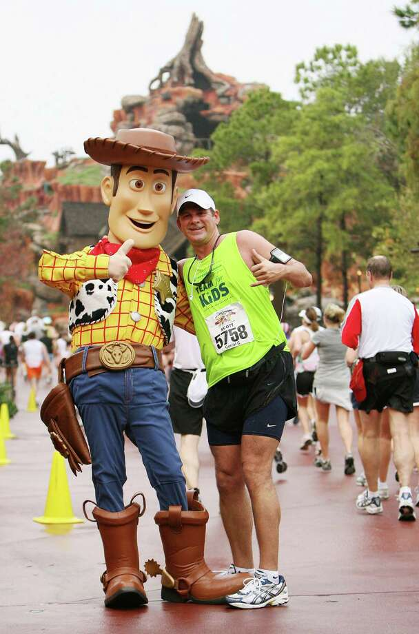 """Athletes pose with characters (Woody from """"Toy Story"""") and run through Frontierland in the Magic Kingdom in Lake Buena Vista, Fla. Jan.13, 2008, in the 15th Annual Walt Disney World Marathon. More than 18,000 registered for the race, an event record. Photo: Todd Anderson /Walt Disney World / Walt Disney World"""