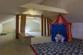 This discreet loft attached to a guest bedroom is a versatile space that could host a children's play room.�