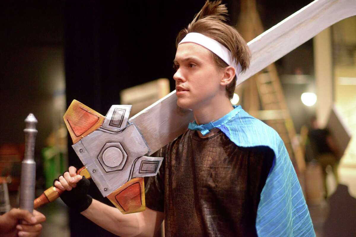 Connor Burton holds a large prop sword during a rehearsal for