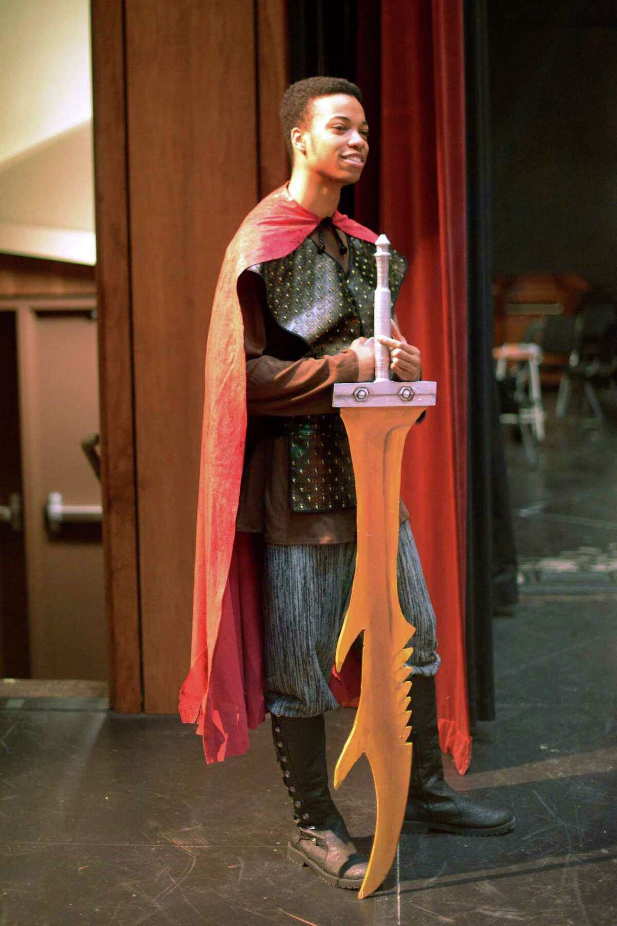Tristan Cowley holds a large sword before a rehearsal for