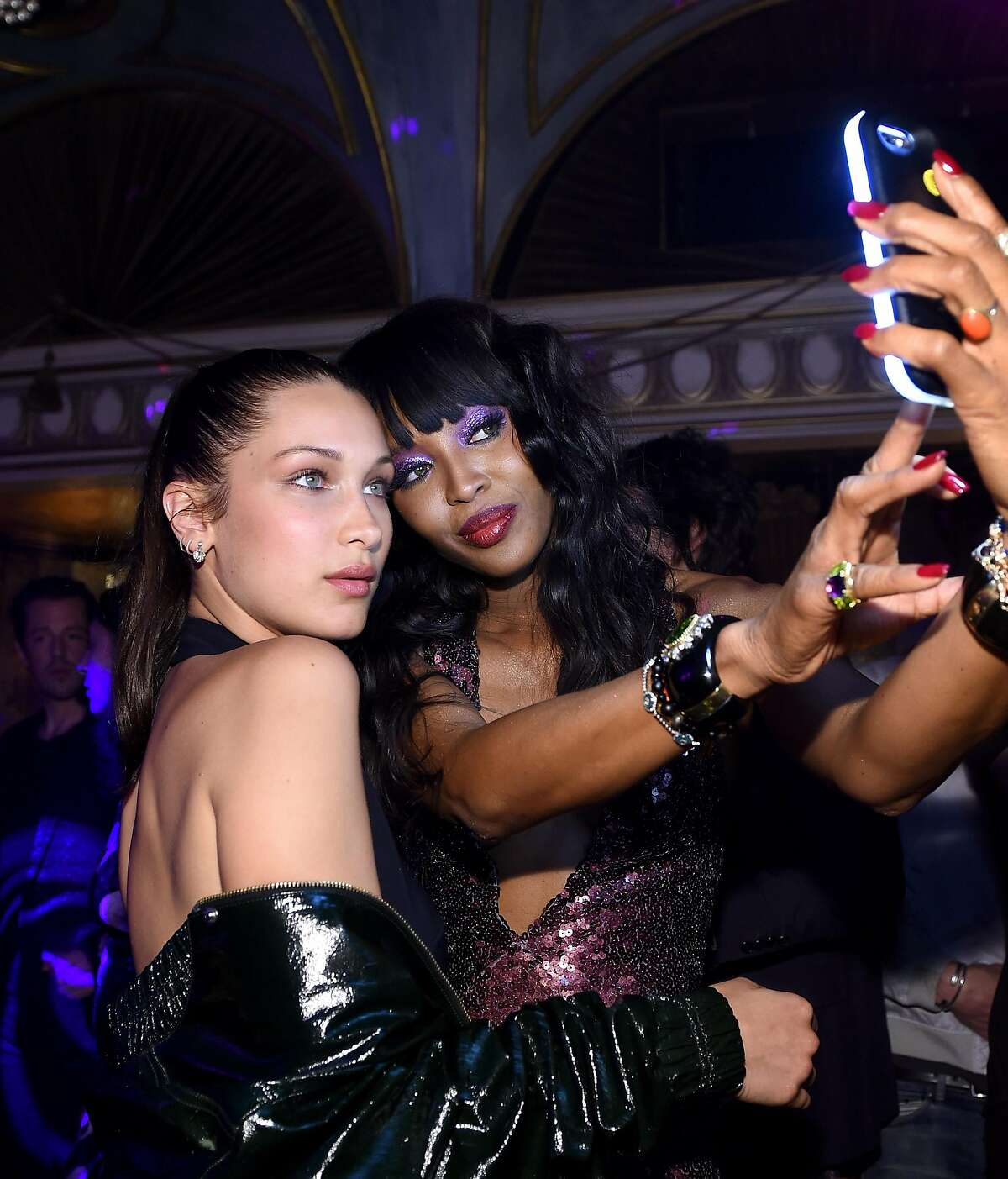 NEW YORK, NEW YORK - APRIL 07: Bella Hadid (L) and Naomi Campbell take a selfie as Marc Jacobs & Benedikt Taschen celebrate NAOMI at The Diamond Horseshoe on April 7, 2016 in New York City. (Photo by Dimitrios Kambouris/Getty Images for Marc Jacobs International, LLC)