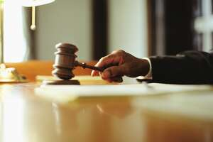 File photo of courtroom gavel. Male judge striking gavel in courtroom, close-up