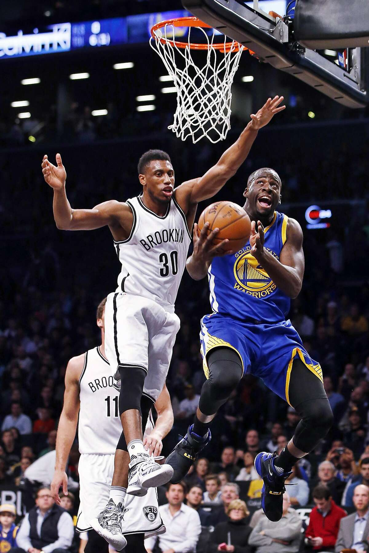 Brooklyn Nets forward Thaddeus Young (30) defends Golden State Warriors forward Draymond Green (23) in the first half of an NBA basketball game, Sunday, Dec. 6, 2015, in New York. (AP Photo/Kathy Willens)