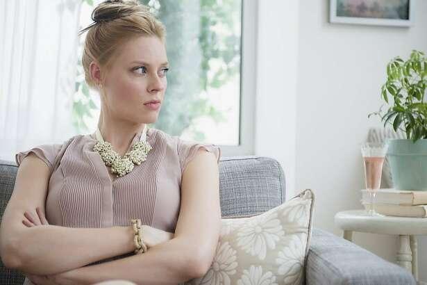 USA, New Jersey, Jersey City, Upset young woman sitting on sofa